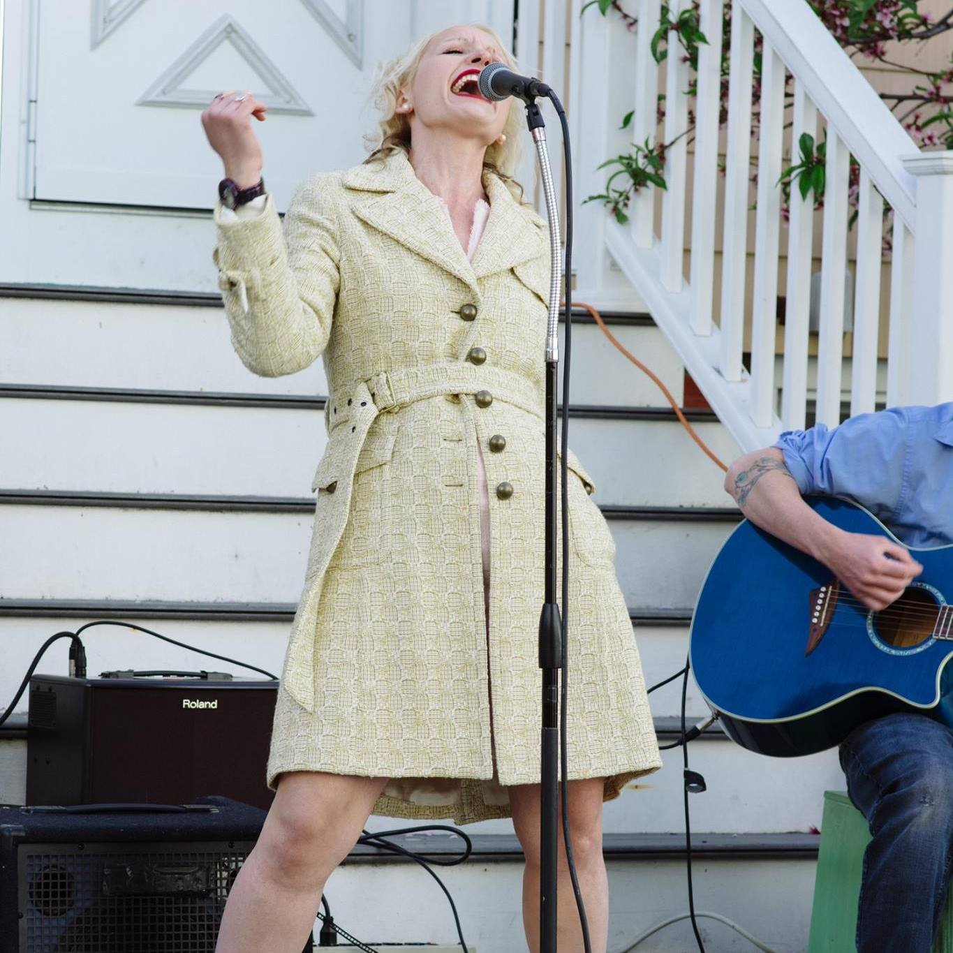 Somerville City Councilor-at-Large Kristen Strezo singing enthusiastically into a microphone at Somerville Porchfest 2018