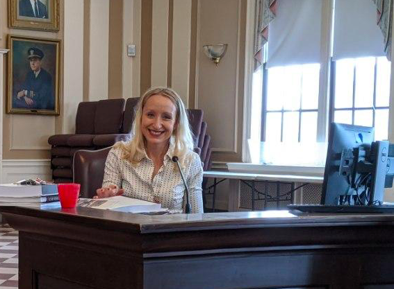 Somerville city councilor-at-large Kristen Strezo sits at her desk in city hall, smiling at the camera
